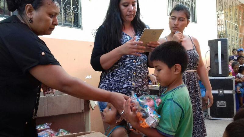 Un niño recibe juguetes de manos de una vocal del comité de su barrio en San Mateo de Manta. Manabí, Ecuador.