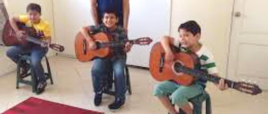 Niños de Montecristi aprenden música ejecutada con guitarra. Manabí, Ecuador.