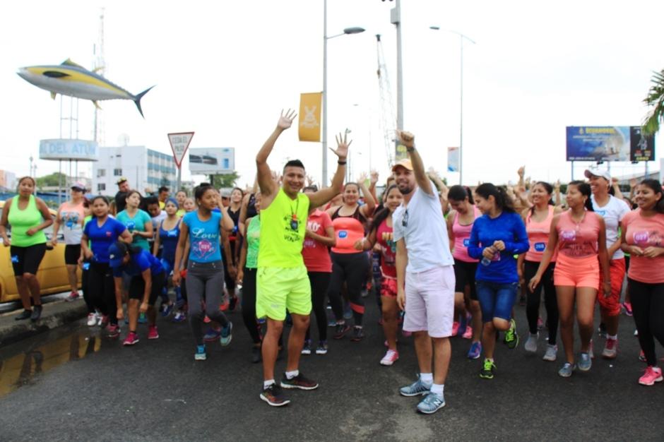 Damas de Manta, con sus entrenadores al frente, celebran su preparación para competir en la carrera Diosa Umiña 5K. Manabí, Ecuador.