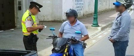 Un motociclista es detenido por la Policía para verificar que porta sus documentos en regla. Manabí, Ecuador.