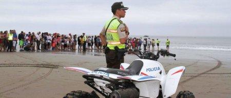 Un policía vigila a un grupo de turistas en una playa de mar. Manabí, Ecuador.
