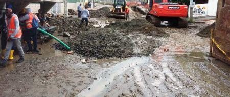 Obreros y maquinaria municipal de Manta reparan una calle después de la lluvia. Manabí, Ecuador.