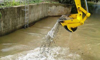 Una excavadora mecánica retirar sedimentos de un estanque de agua de río para potabilizar, Caza Lagarto, Santa Ana. Manabí, Ecuador.