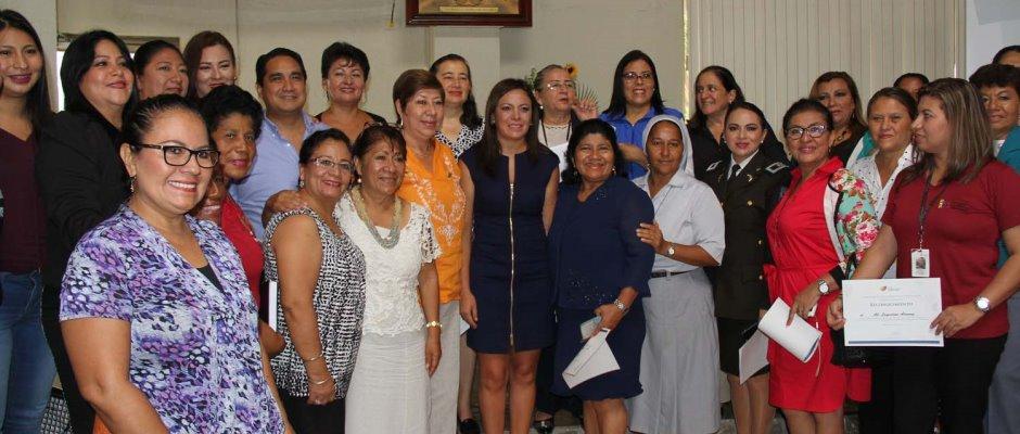 La Ministra de Justicia posa con un grupo de personas que trabajan para erradicar la violencia intrafamiliar en Manabí, Ecuador.