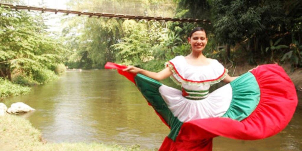 Una artista baila una pieza folclórica de Manabí al borde de un río (Foto tomada del sitio web del GAD provincial). Manabí, Ecuador.