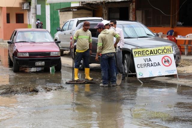 Obreros de la EPAM destupen un pozo de revisión de alcantarilla en el Barrio Jocay. Manabí, Ecuador.