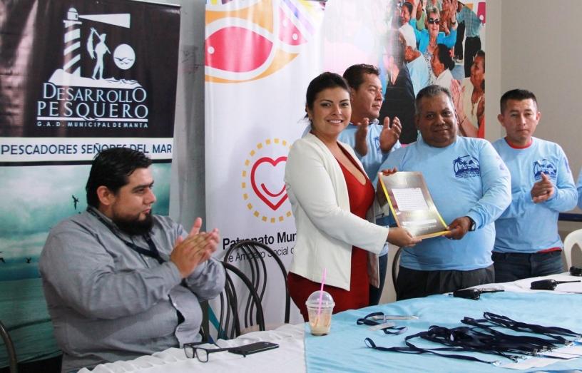 La subdirectora de emprendimiento productivo del Patronato municipal de Manta, Mery Chong, entrega el Estatuto del gremio de transportistas del Muelle Flotante a su presidente Luis Barahona. Manabí, Ecuador.