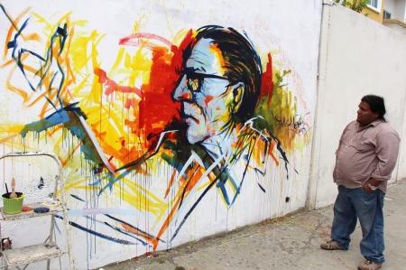Efigie de Hugo Mayo en un mural en Manta. Lo observa su autor, Freddy Fiallos (Dadá).