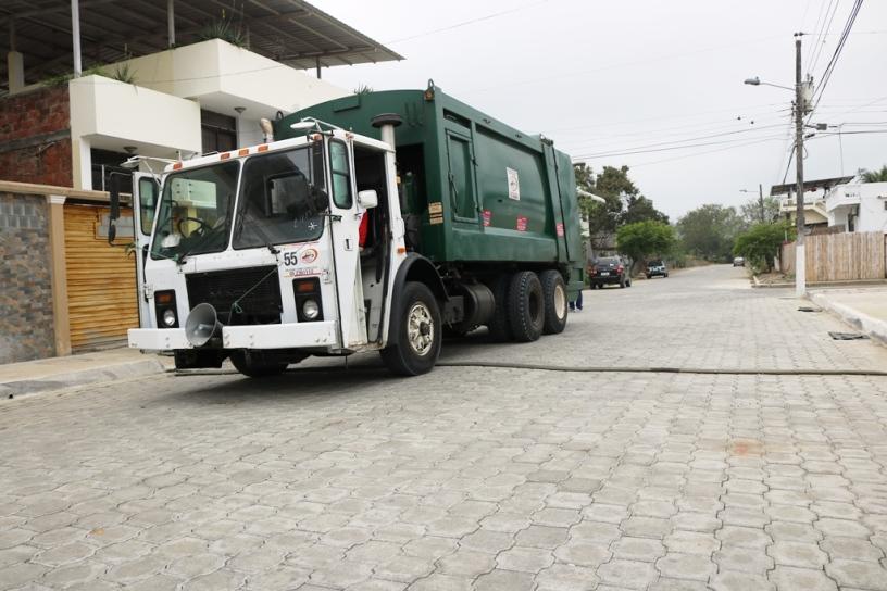 Un camión municipal recoge basura de los hogares que están a ambos lados de esta calle de Chone. Manabí, Ecuador.