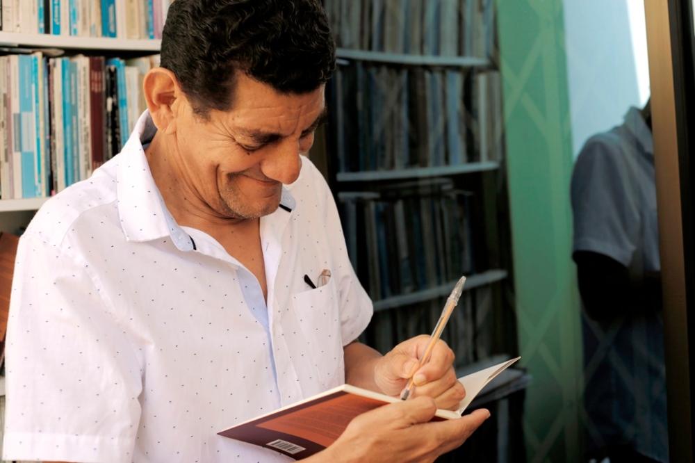 Gustavo Cañizares rubrica uno de sus poemarios más recientes. Manabí, Ecuador.