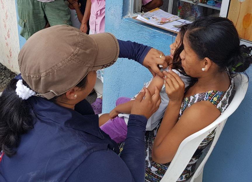 Brigadista de salud vacuna contra la gripe a una niña menor de edad. Manabí, Ecuador.