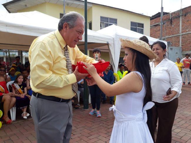 La niña danzante obsequia frutos dulces al alcalde Deyton Alcívar.
