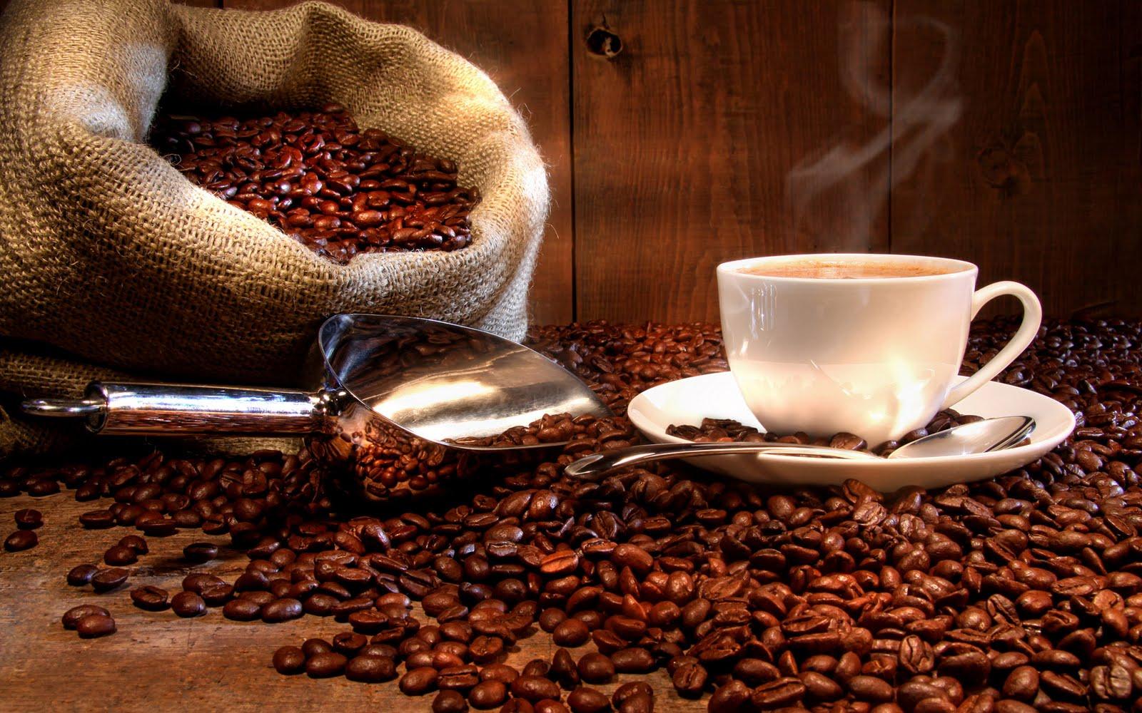 Una taza con café caliente, encima de granos tostados de este producto agrícola tan apetecido en el mundo. Manabí, Ecuador.