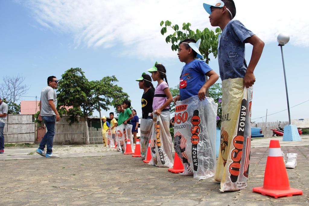 Niños participan en una carrera de ensacados organizada por el Patronato municipal de Manta. Manabí, Ecuador.