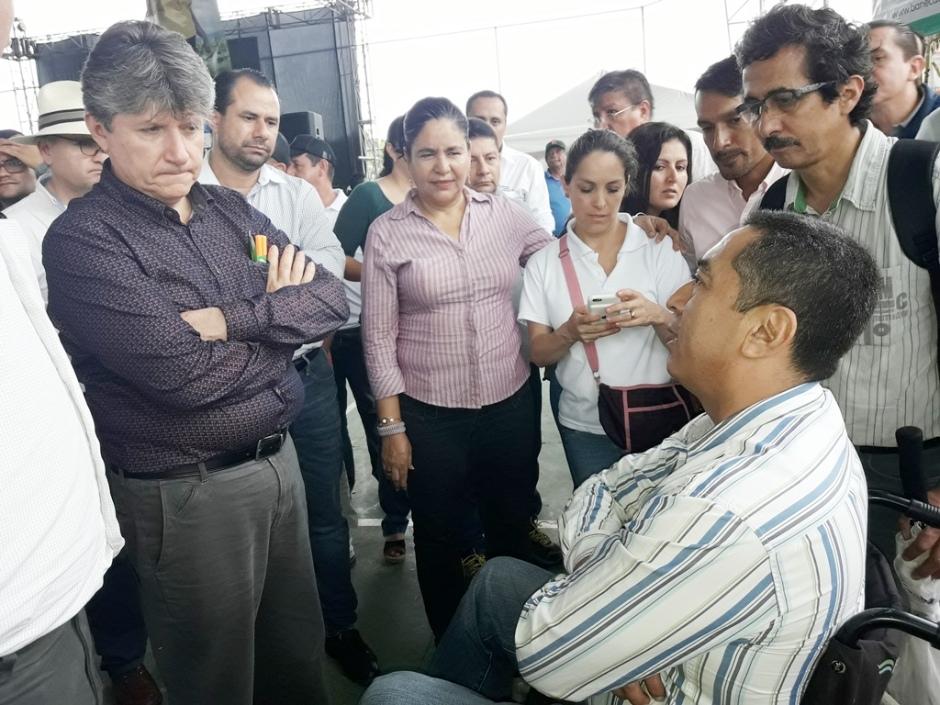 El ministro de Agricultura y Ganadería, Rubén Flores Agreda, conversa con un productor agropecuario postrado en una silla rodante. Manabí, Ecuador.