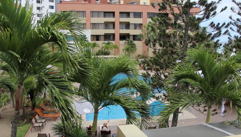 Vista de una piscina entre palmeras, en un hotel de Manta. Manabí, Ecuador.