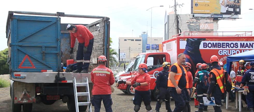 Bomberos de Manta y delegados de Bomberos Unidos Sin Fronteras, de España, en un momento previo a un simulacro de salvamento en una estructura colapsada. Manabí, Ecuador.