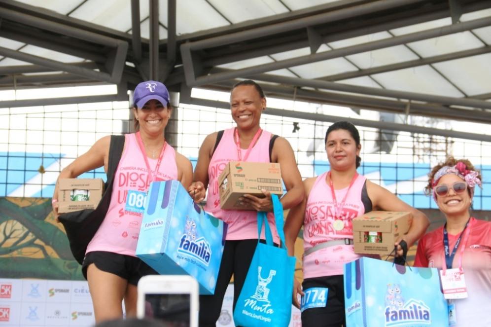 Tres de las ganadoras, cada una con su respectivo premio que les entregó Simoné Delgado, sonriente, a la derecha de la foto.