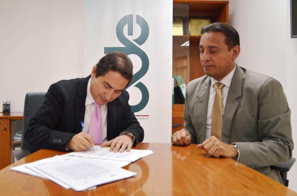 Ignacio Mendoza, gerente del BDE en Manabí, suscribe el convenio de crédito para construir el mercado de Charapotó. Observa Manuel Gilces, alcalde del Cantón Sucre. Manabí, Ecuador.