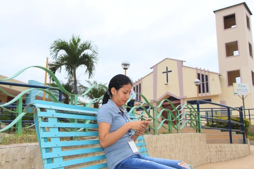 Una mujer conecta su teléfono móvil al wi-fi público gratuito disponible en la zona rural del Cantón Manta. Manabí, Ecuador.