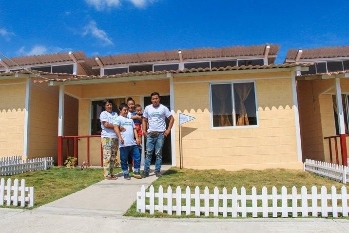 Miembros de una familia adjudicataria de vivienda posan al frente de su nuevo hogar en Ceibo Renacer, Manta.