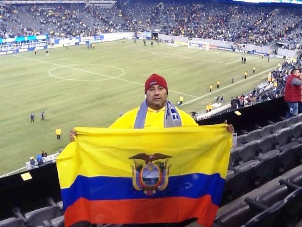 Joselías Sánchez junior muestra la bandera del Ecuador dentro de un estadio de fútbol.