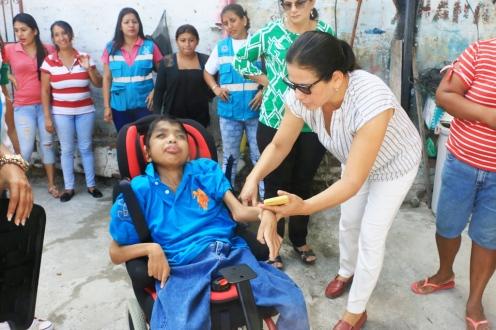 La presidenta del Patronato de Amparo Social de Manta ayuda a este joven discapacitado para que se acomode en la flamante silla con ruedas que le llevó la dignataria.
