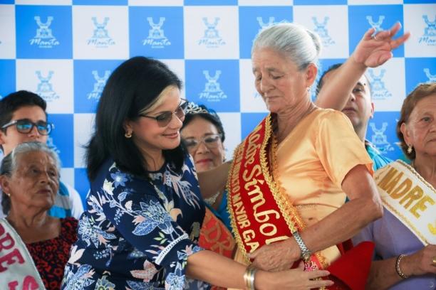 Esperanza Álava, el momento de su investidura como Madre Símbolo 2018. Ciñe la banda, Tatiana Zambrano, directora ejecutiva del Patronato Municipal de Amparo Social de Manta.