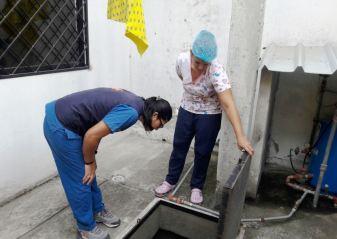 Inspeccionando que el agua del aljibe no tenga larvas del mosquito.