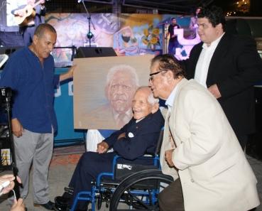 Carlos Rubira Infante recibe su retrato, pintado por el artista Ivo Uquillas (izquierda) la misma noche del homenaje al músico.