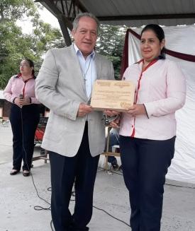 La educadora Ivette Arteaga entregó un diploma por la acción cívica del alcalde Deyton Alcívar, que lo recibe.
