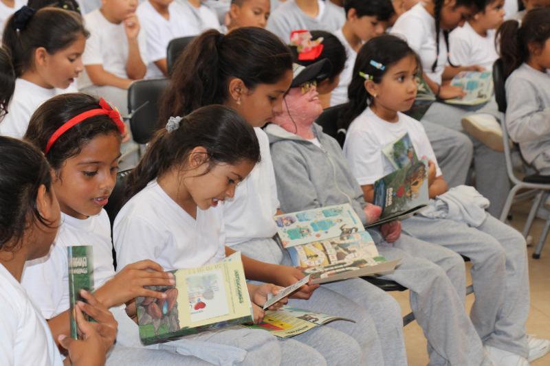 """Niños que estudian en la Unidad Educativa Réplica Manta observan absortos el libro didáctico de la campaña motivadora """"Agua ConCiencia"""" de Epam-Veolia. Manabí, Ecuador."""
