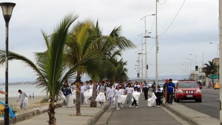 Estudiantes de secundaria recogen basura mientras caminan por una vía de Manta. Manabí, Ecuador.