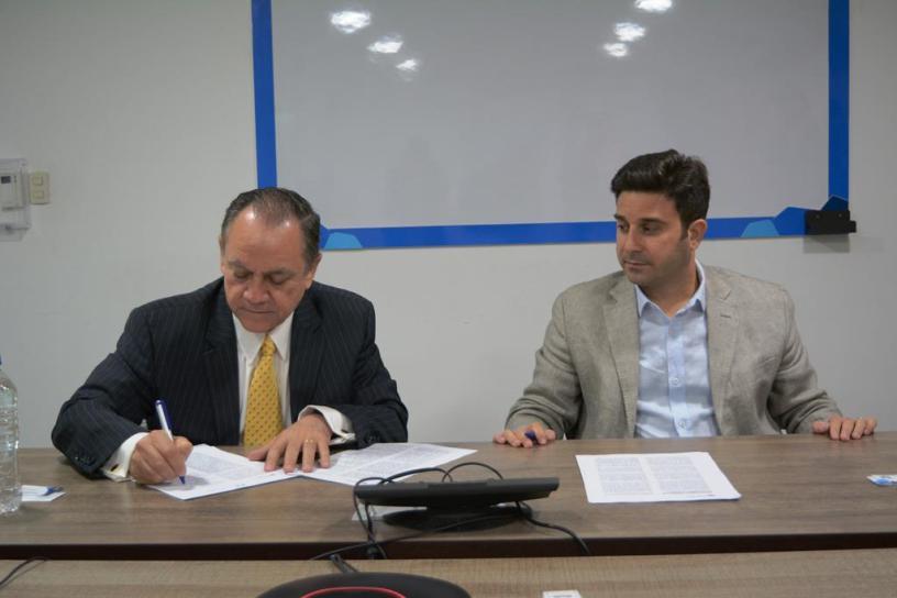 Mario Ayala, presidente alterno de la Cámara de Industrias de Guayaquil, firma el convenio; lo observa Matías Laks, CEO de Unilever. Guayaquil, Ecuador.