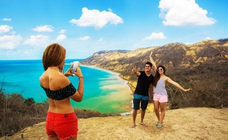 Tres jóvenes turistas hacen fotos en un rincón marino de la zona rural del Cantón Manta. Manabí, Ecuador.