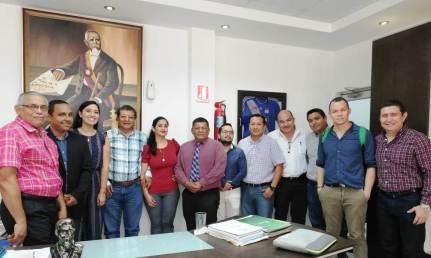 El alcalde de Montecristi (camisa de rayas verdes) posa en su despacho con la delegación de la Facultad de Hotelería y Turismo de la Uleam de Manta.