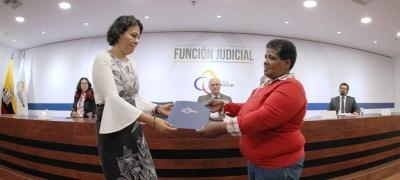 Daira Olinda Portocarrero Hurtado (der.) recibe el Acuerdo con las disculpas públicas del Consejo de la Judicatura. Quito, Ecuador.
