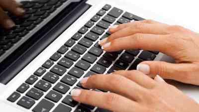 Escribiendo con ordenador portable.