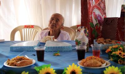 María Natividad Calderón Reyes se apresta a servirse la torta por sus 118 años de vida, homenaje que le brindó el Patronato municipal de Manta. Manabí, Ecuador.