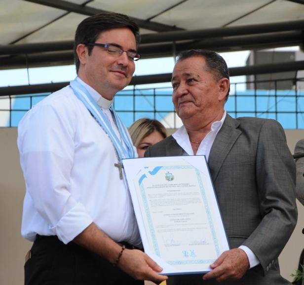 El vicealcalde de Manta, Eduardo Velásquez García, entrega la Condecoración Umiña del Concejo municipal al sacerdote André Drouet Salcedo. Manabí, Ecuador.