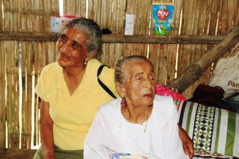 Yolanda y María Natividad escuchan las felicitaciones que formulan los miembros de la delegación del Patronato municipal de Manta.